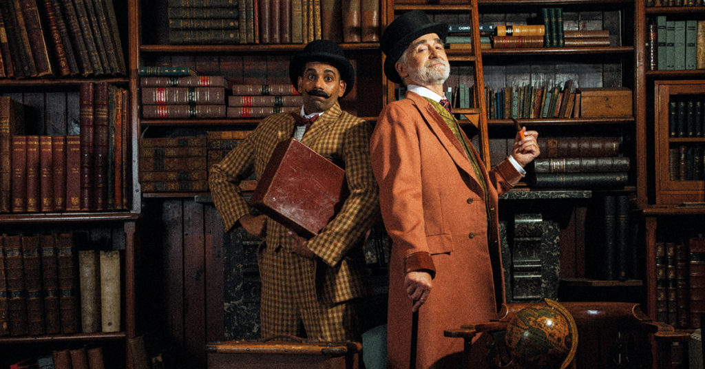 Two men (Darren Kuppan and Robert Pickavance) in Victorian costume, one with a moustache, bowler hat and suitcase and one with a top hat, beard and pipe.